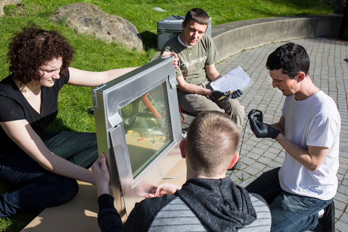 four people work on a solar window outside