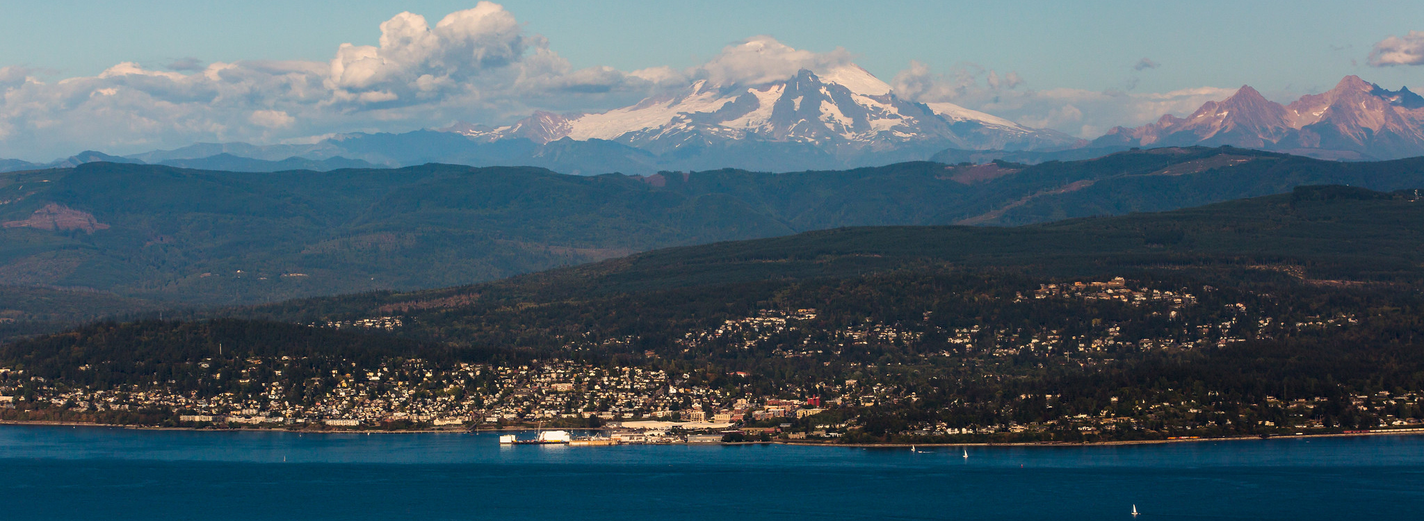 Aerial photo of Bellingham, Bellingham Bay, and Mount Baker. Bellingham is nestled in the hills and valleys between the bay and the mountains.