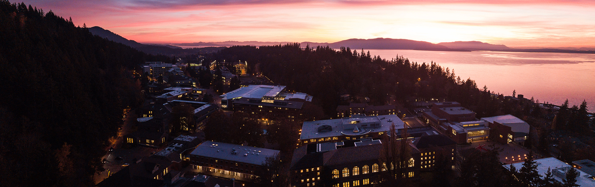 Evening shot of campus by drone. The bay and sky are pink and purple. The windows of the buildings glow gold with the fading light of the sun.