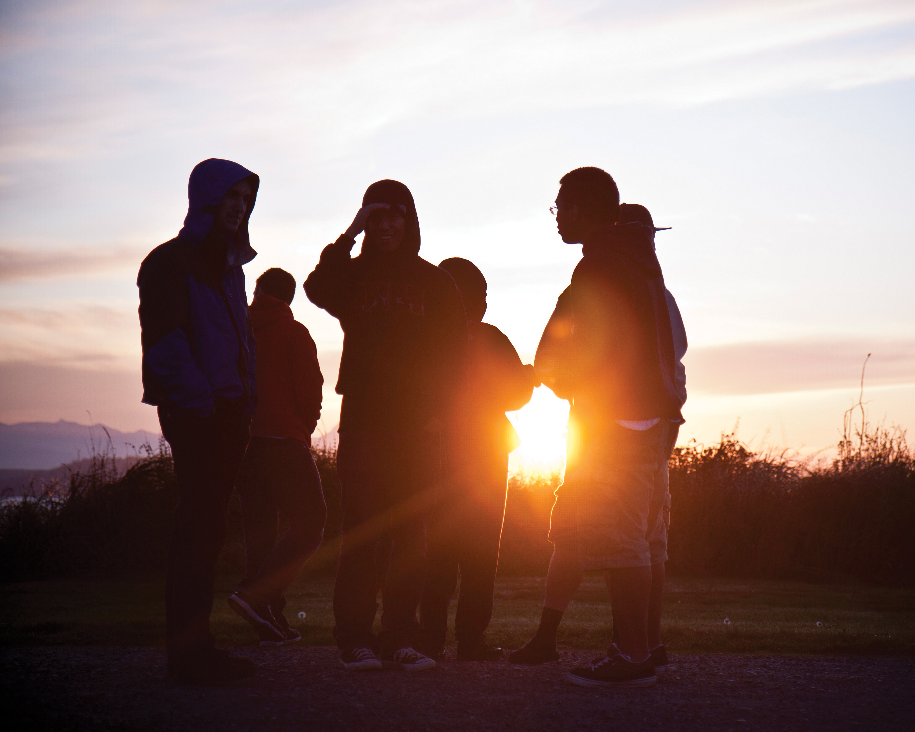 Silhouette of a group of students with the sun setting behind them.