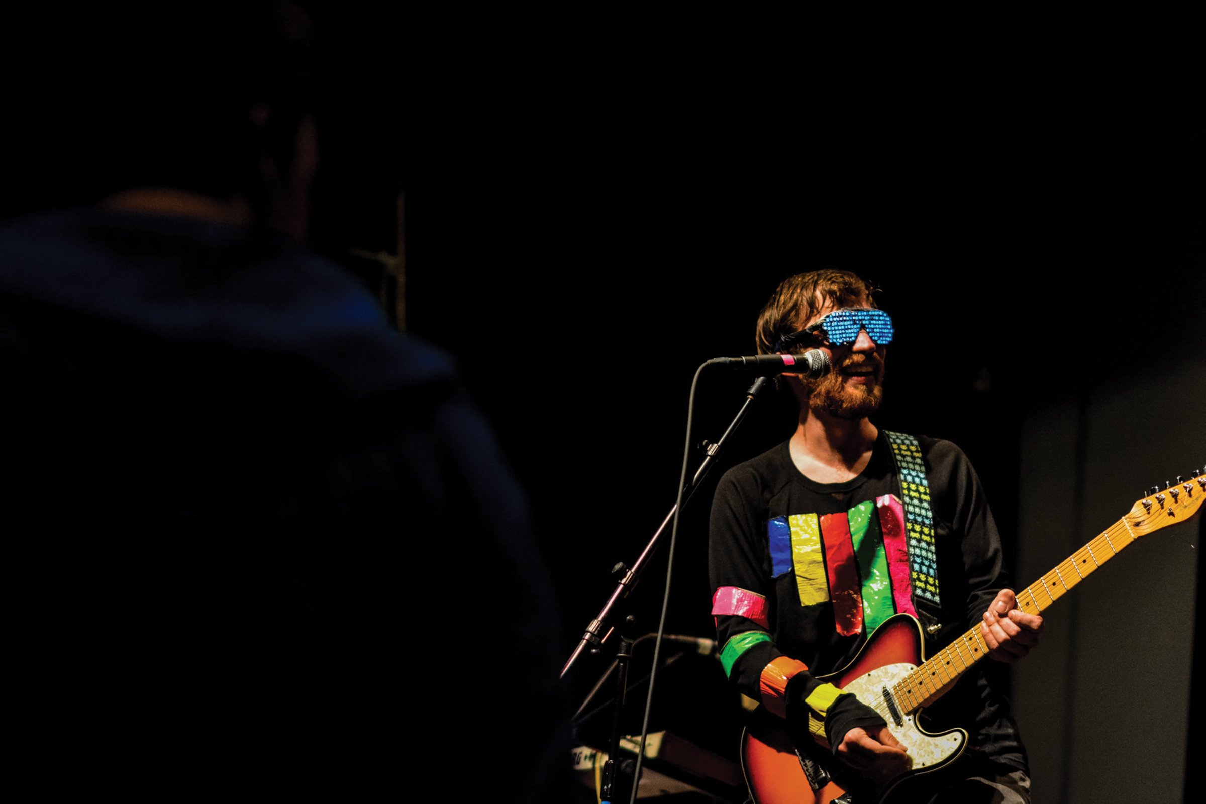A man wearing silly sunglasses and playing the guitar