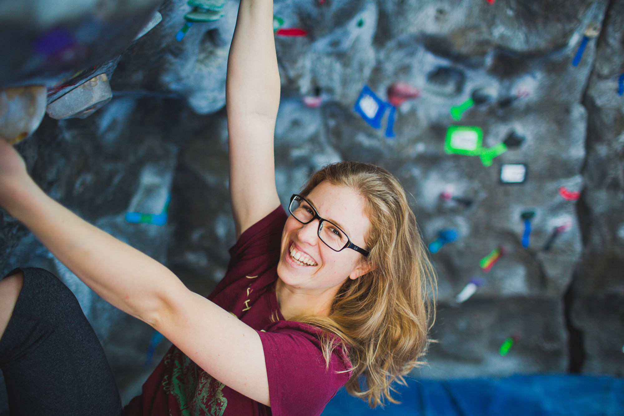 Smiling, Kyla Hall hangs from the climbing wall in the Wade King Student Rec Center.