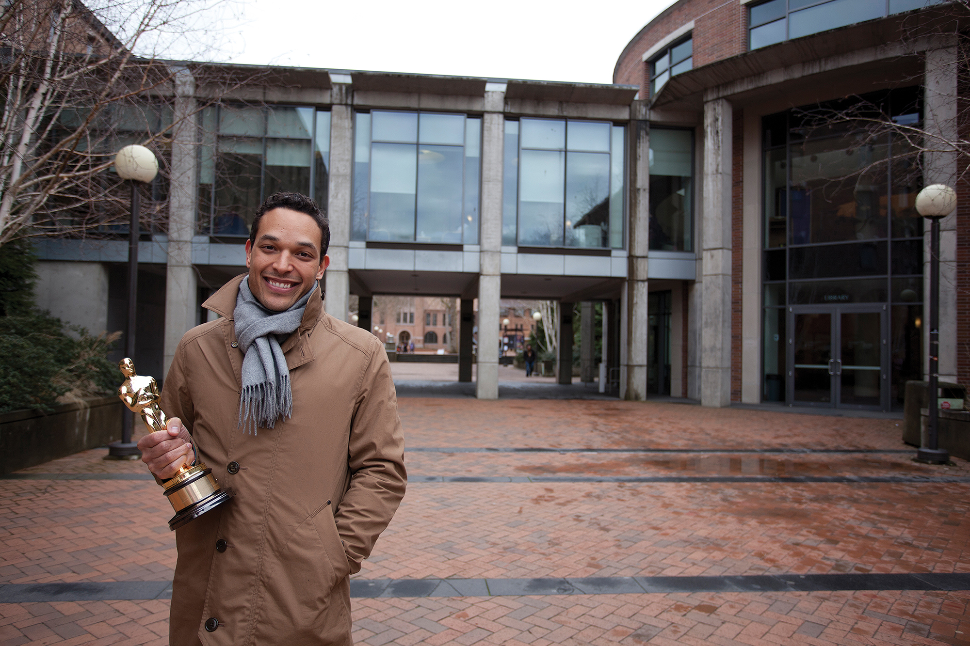 Alumni TJ Martin poses with their Academy Award in front of the Western Washington University library. Tj is smiling, with one hand gripping the award close to their chest and the other hand tucked into their thick winter coat.