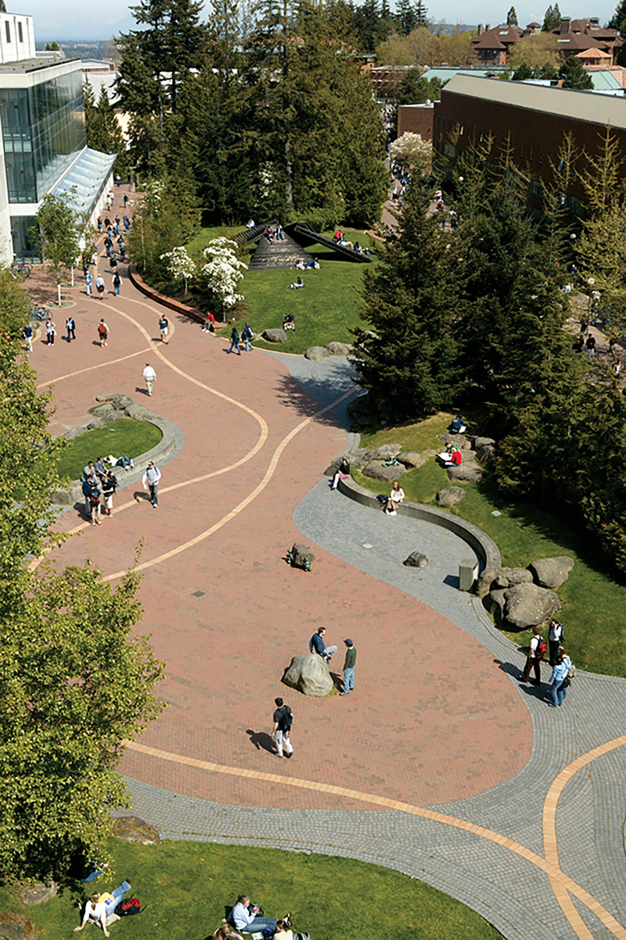 An image taken from a drone, looking down onto students walking along the wide paths between some of WWU's campus buildings. Some students are standing in groups, some sitting on benches along the path, and others are presumably walking to their next class.