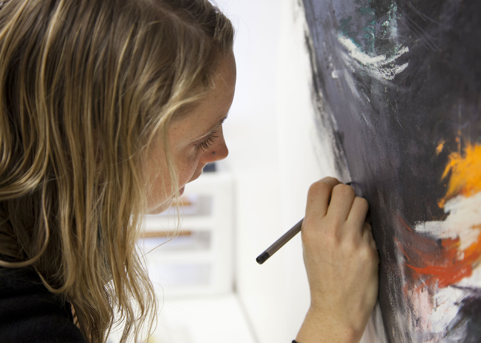 A student leans closely into a large, painted canvas, adding small details with a pencil.