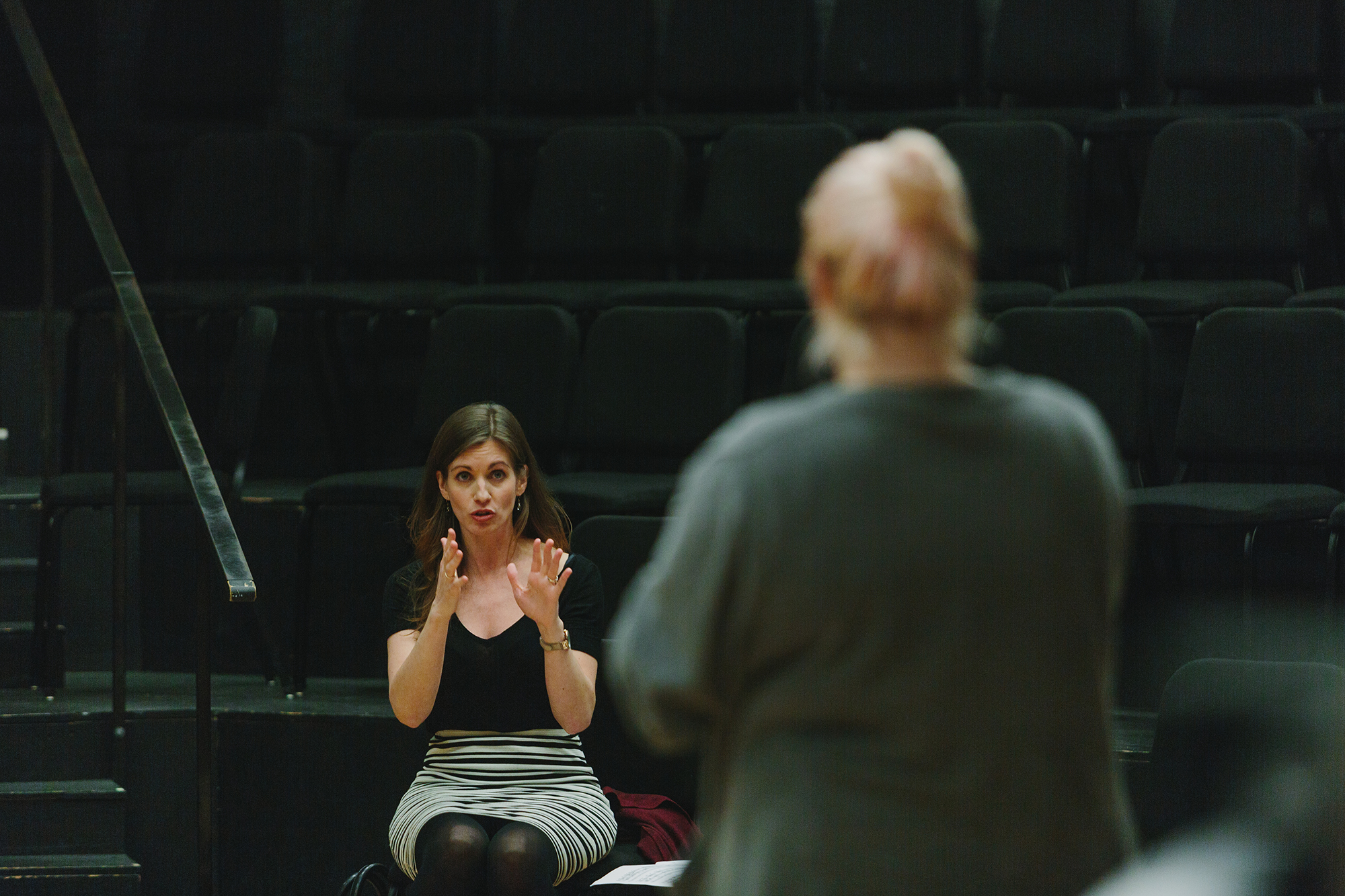 A teacher in the background sits in an empty auditorium row, speaking to a student standing on stage in the foreground.