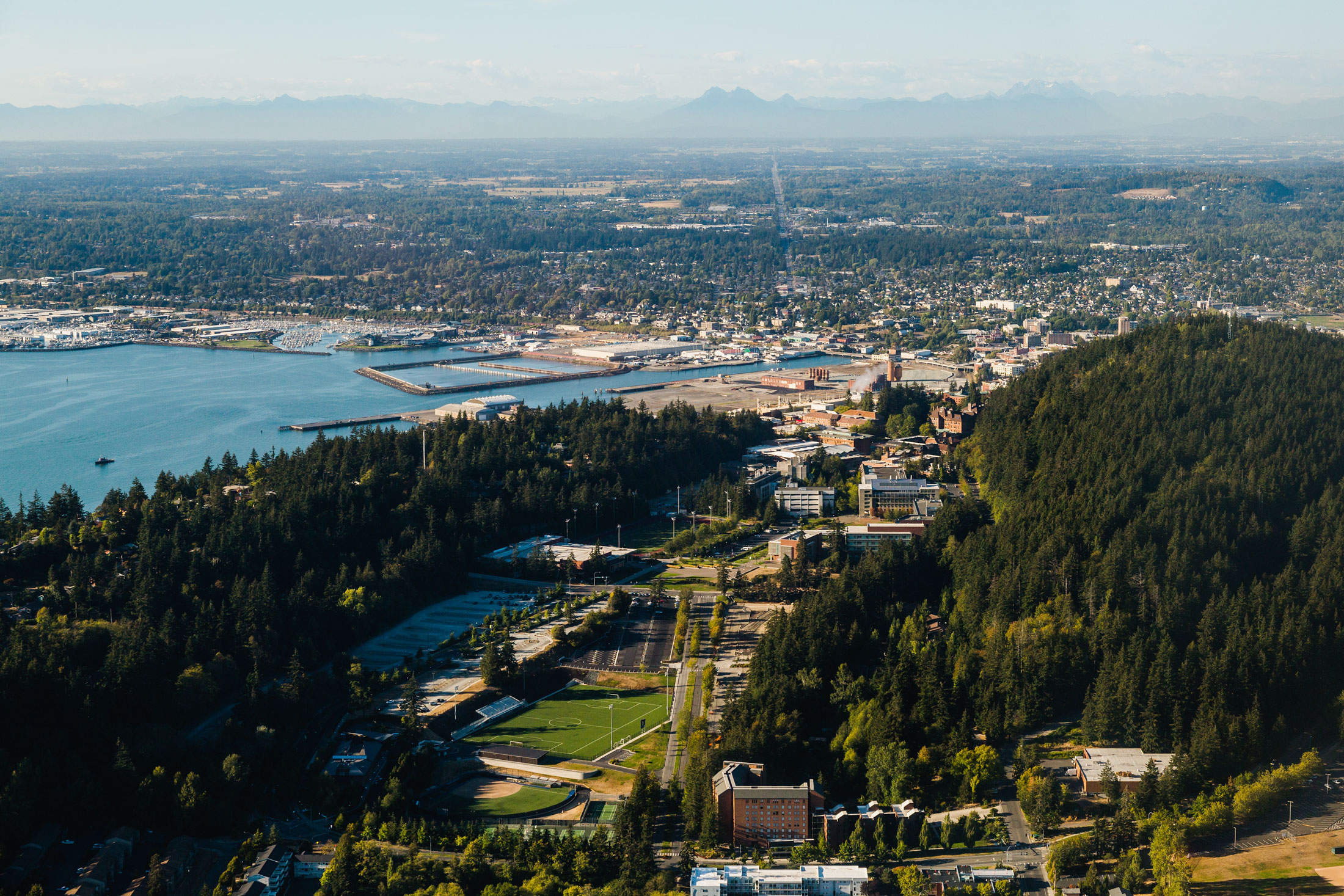 An aerial view of WWU campus in the foreground and Downtown Bellingham in the background. To the left is the bay and far in the back is a ridge of mountains on the skyline, peaking through the mid-day haze.