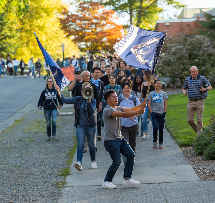 First-Year students are led by a WWU flag carrying student as they march towards downtown Bellingham for the annual Paint B'ham Blue event.