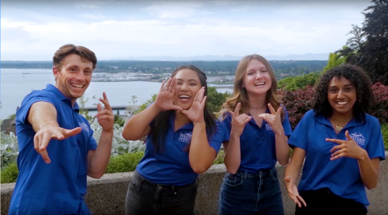 Four student tour guides smiling and having fun making poses for the camera.