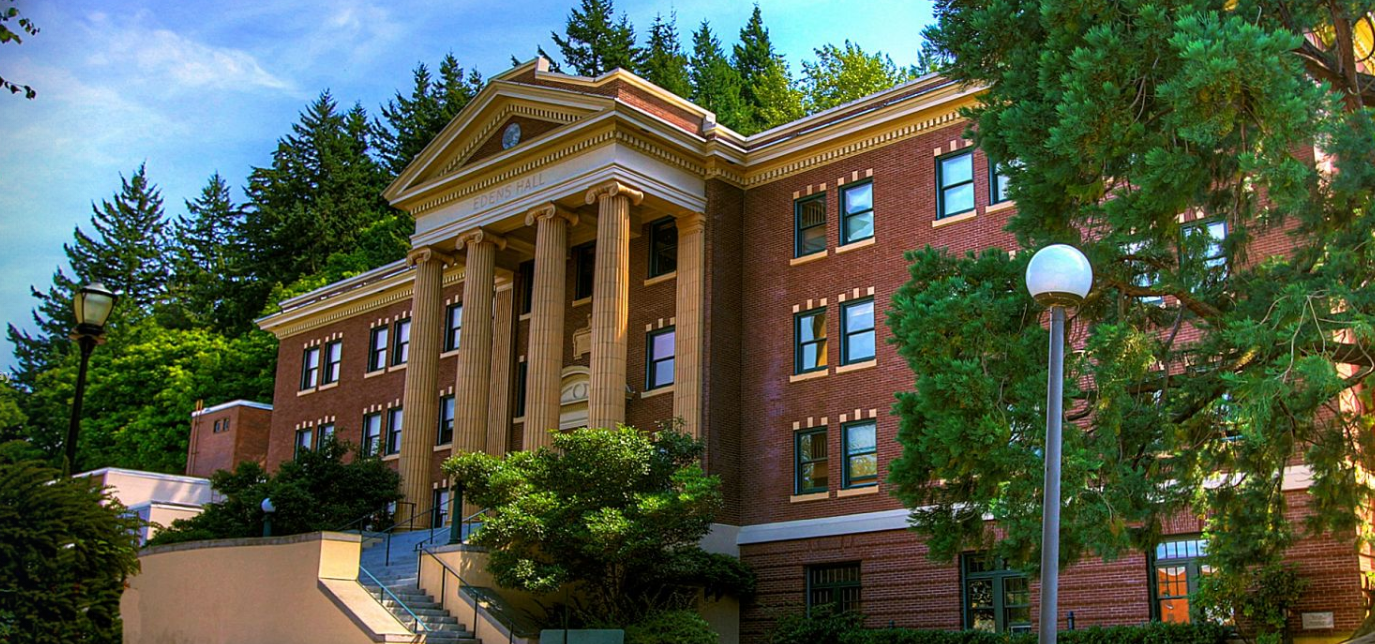 Edens Hall, an ornate dorm building with large columns, surrounded by trees on a sunny day.