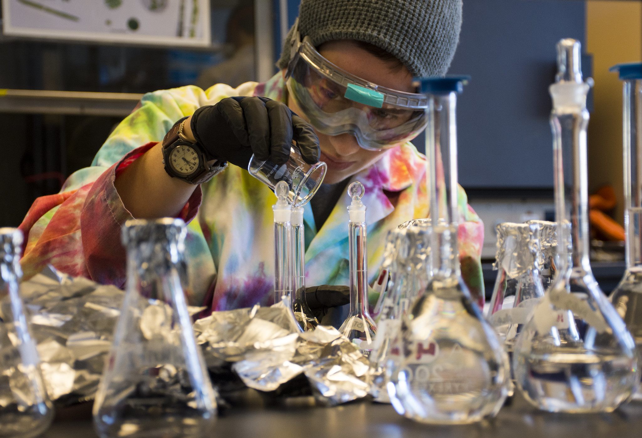 A student in a tie-dyed lab coat uses laboratory glasswear.