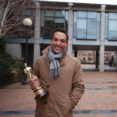 TJ Martin poses in front of the WWU Library with their Academy Award.